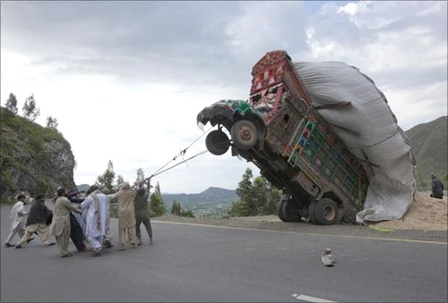 Men use ropes to try and right a supply truck overloaded with wheat straw, used as animal feed, along a road in Dargai, in the Malakand district, northwest of Pakistan's capital Islamabad.