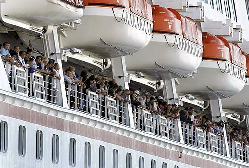 Passengers clap as the Carnival Cruise Lines cruise ship C/V Splendour docks after being towed into San Diego harbour.