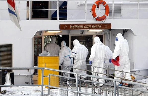 Paramedics dressed in protective attire enter the ship, the Bellriva, in Wiesbaden.