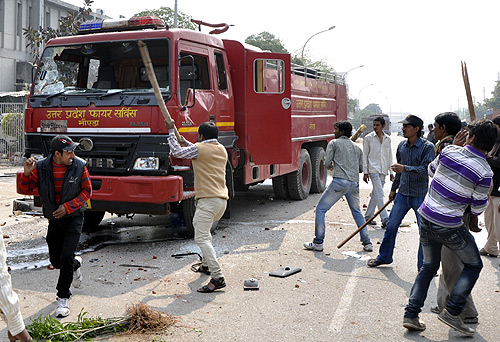 Protesters damage a fire engine during a strike in Noida, on the outskirts of New Delhi.