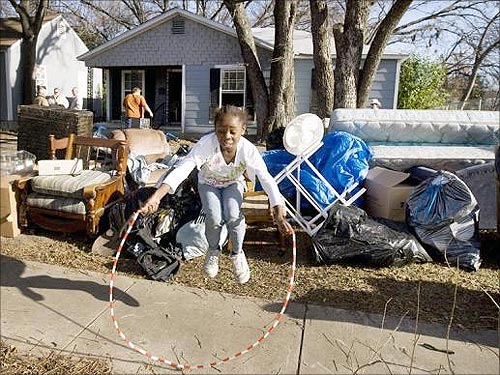 A young girl jumps rope on the sidewalk next to her family's belongings after she, her parents, and her four brothers and sisters, received a court order of eviction due to foreclosure, in Waco, Texas.