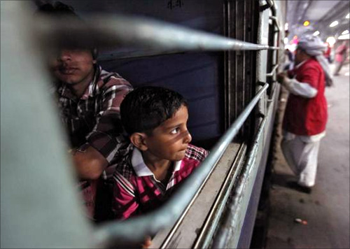 A boy looks out of a compartment of the Kalka Mail passenger train at a railway station in the old quarters of Delhi.