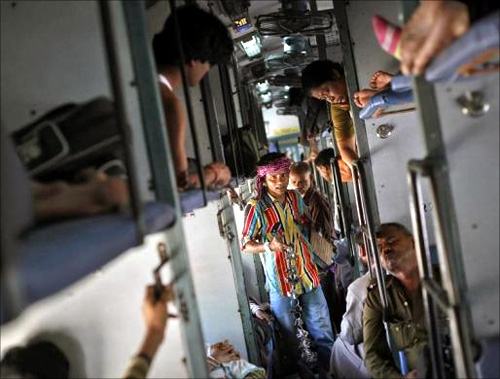 A man sells locks and chains inside a compartment of the Kalka Mail passenger train on the way to Kolkata.