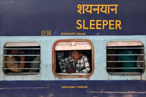 A man looks out of a compartment of the Kalka Mail passenger train at a railway station in Fir