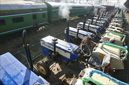A worker checks a tractor loaded on a goods train at a railway yard in the northern Indian city of Chandigarh.