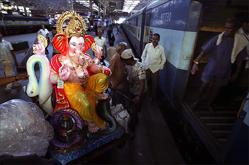 People load an idol of the Hindu elephant God Lord Ganesha onto a train at a railway station in Mumbai.