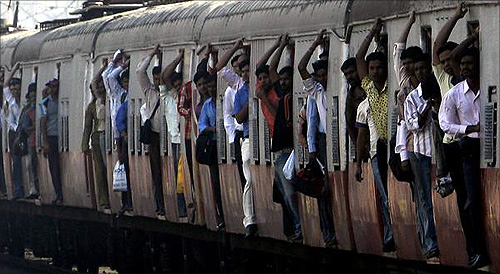Passengers travel in a crowded suburban train at a railway station in Mumbai.