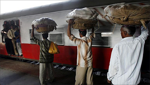 Hawkers carrying baskets of bananas prepare to board a train at a railway station in Mumbai.
