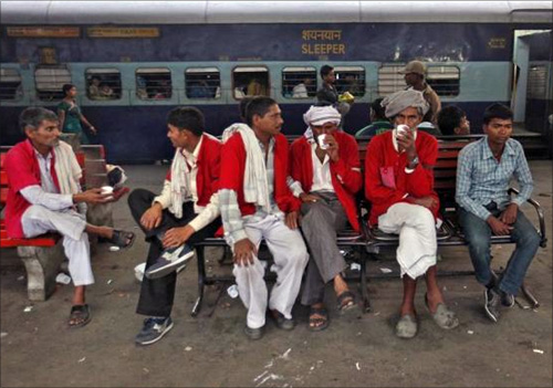 Porters rest in front of the Kalka Mail passenger train at a railway station in the old quarters of Delhi.