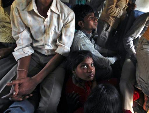Passengers sit on the floor while travelling inside an overcrowded general class compartment of the Kalka Mail train in Kanpur.
