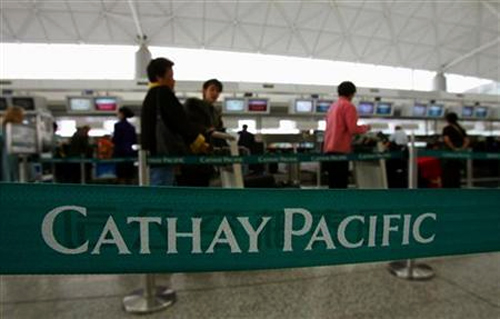 Passengers wait in line at a Cathay Pacific Airways check-in counter at the Hong Kong international airport.