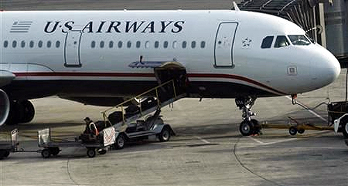 A worker is seen loading luggage on a plane from US Airways at Newark Liberty International Airport in Newark, New Jersey.