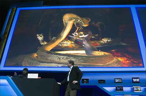 Achin Bhownik (L) demonstrates a computer game with conceptual computing features to Kirk Skaugen, vice president of PC client group for Intel, during an Intel press conference during the Consumer Electronics Show (CES) in Las Vegas.