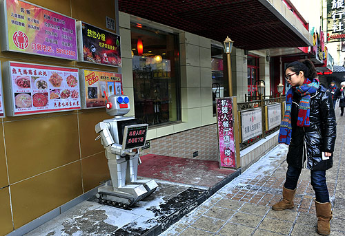 A pedestrian looks at a robot that specialises in greeting people outside a Robot Restaurant in Harbin, Heilongjiang province.