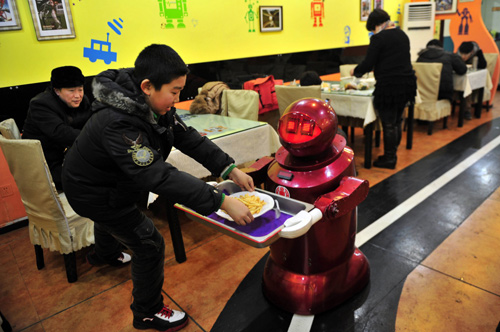 A robot that specialises in delivering food serves a customer with French fries at a Robot Restaurant in Harbin, Heilongjiang province.