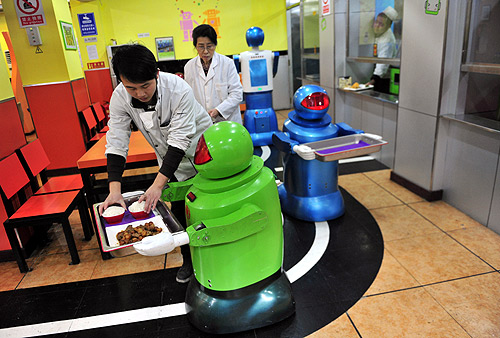 A robot that specialises in delivering food holds a tray as a waiter puts dishes on it at a Robot Restaurant in Harbin, Heilongjiang province.