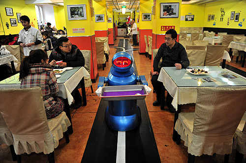 A robot that specialises in delivering food holds an empty plate after serving meals to customers at a Robot Restaurant in Harbin, Heilongjiang province.