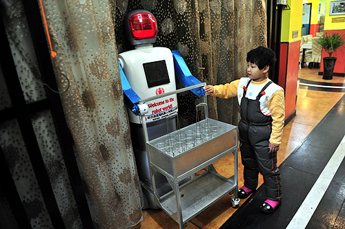 A boy touches a robot that specialises in delivering drinks at a Robot Restaurant in Harbin, Heilongjiang province.