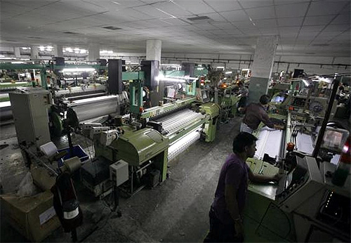 Employees work inside a linen cloth weaving unit at Palsana village, on the outskirts of Surat, in Gujarat