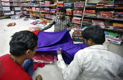 A shopkeeper displays a saree, a traditional Indian garment for women, to customers inside a shop at Surat, in Gujarat.