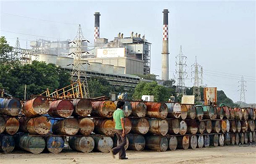 A man walks past the thermal power plant of Torrent Power on the outskirts of Ahmedabad.