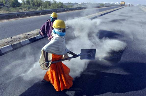 A woman labourer spreads black ash over a newly constructed road at Raipur village, in Gujarat.