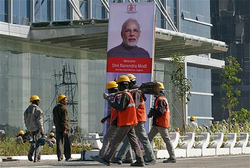 Workers walk past a poster of Gujarat's Chief Minister Narendra Modi installed at the construction site of Gujarat International Finance Tec-City (GIFT) building at Gandhinagar, in Gujarat.
