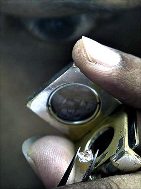 An employee inspects diamonds while grading them.