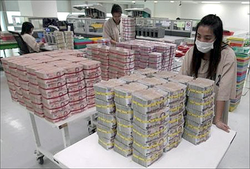 A bank employee gathers Thai baht notes at Kasikornbank in Bangkok.