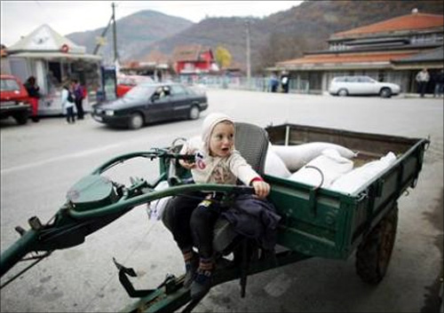 A boy waits for his father as he sits in their vehicle in the southern Serbian town of Trgoviste.