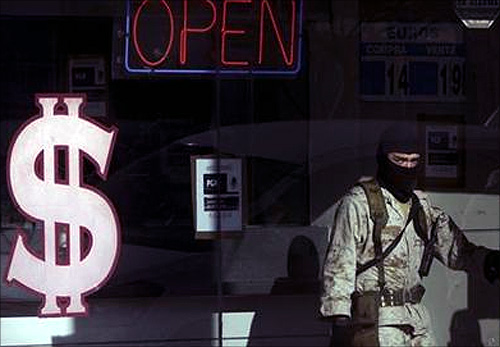 A soldier stands inside a raided pawn shop while under investigation for money laundering in Tijuana.