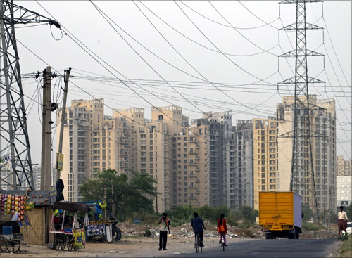 People ride their bicycles under overhead power cables, against the backdrop of multi-story residential apartments at Gurgaon.
