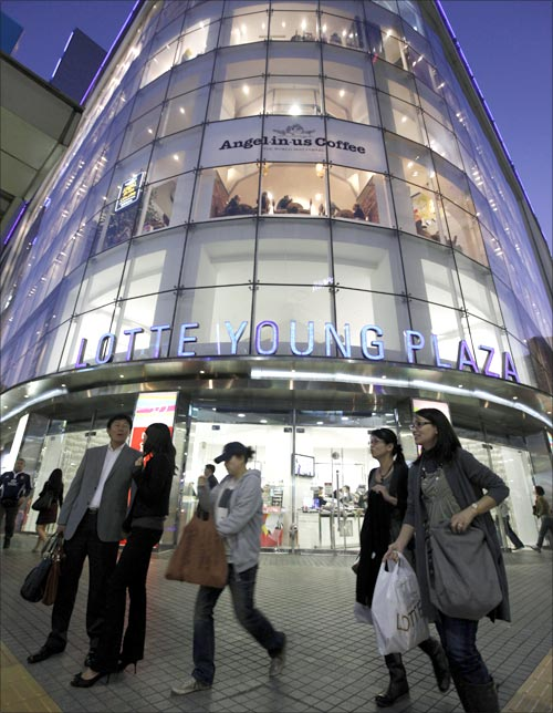 People walk past a Lotte Shopping mall in Seoul.