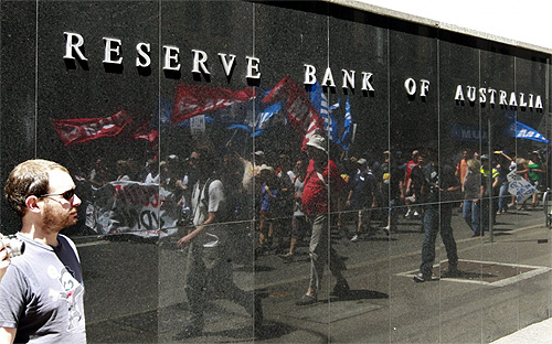 Sun reflects off the front door sign of the Reserve Bank of Australia building in Sydney.