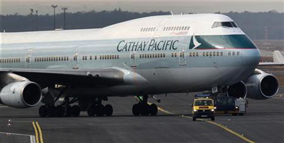 An airport apron controller vehicle is pictured in front of a Cathay Pacific Boeing B747-400 Aircraft on the runway at Frankfurt's airport.