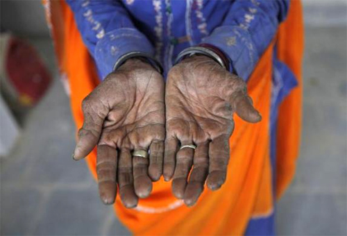 Radha, 75, a vegetable vendor poses with her hands after she got her fingerprint scanned for the Unique Identification (UID) database system at an enrolment centre at Merta district in Rajasthan.