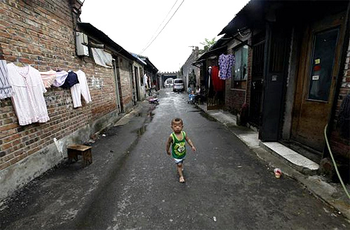 A boy walks past houses in a residential area for migrant workers in Beijing.