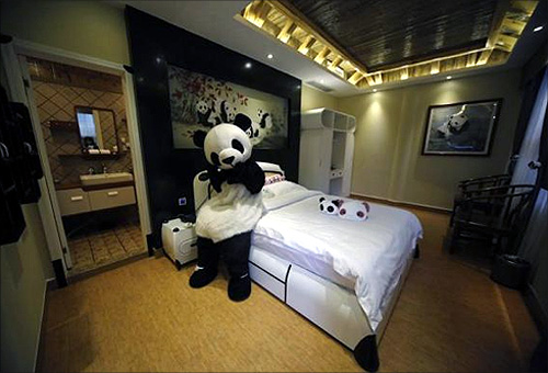 An employee dressed in a panda costume poses for a photo during the soft opening of a panda-themed hotel at the foot of Emei Mountain, Southwest China's Sichuan province.