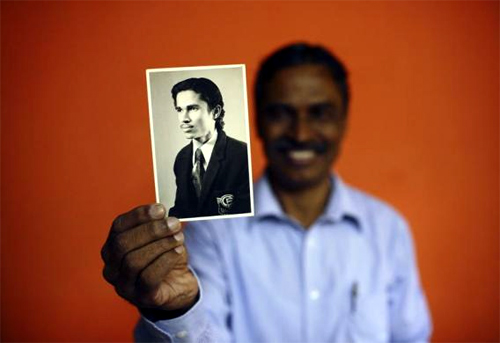 Train driver TS Unnikrishnan Nair, 60, who has been working for Indian Railways for 40 years, shows a picture taken when he first started his job, at his apartment in Mumbai.
