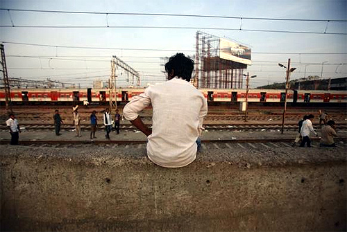 A man sits on a wall near the tracks of Bandra Railway station in Mumbai.