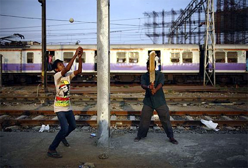 Boys play cricket along the tracks as a suburban train passes by, near Bandra railway station in Mumbai.