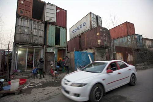 People stand outside shipping containers serving as their accommodation, as a car passes through a street, in Shanghai.
