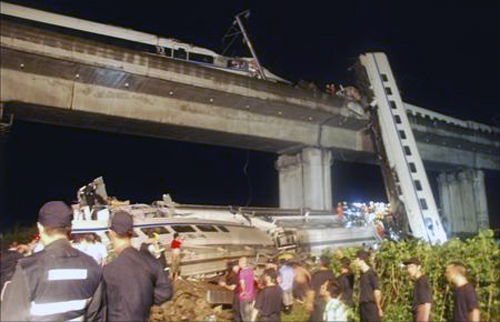 Rescuers carry out rescue operations after two carriages from a bullet train derailed and fell off a bridge in Wenzhou, Zhejiang.