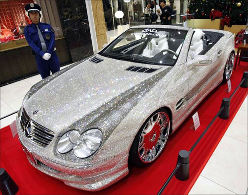 A Mercedez-Benz SL600 series shimmering with Swarovski crystal glass is displayed as a security person stands guard at Sogo department store in Osaka.