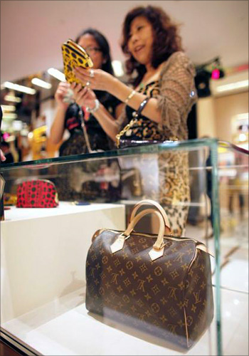 A woman shops in a Louis Vuitton store during Vogue's 4th Fashion's Night Out in downtown Shanghai.