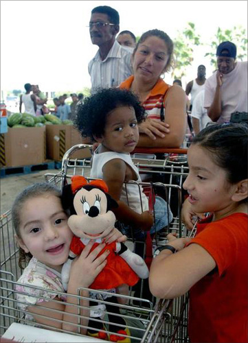 Samantha Cerda (L), 3, holds up her Minnie Mouse as she, Tatiana Jackson (C), Tabihta Cerda (R), and Juanita Valdez (middle rear) wait in line at the HEB Gulfgate Grocery store in Houston, Texas.