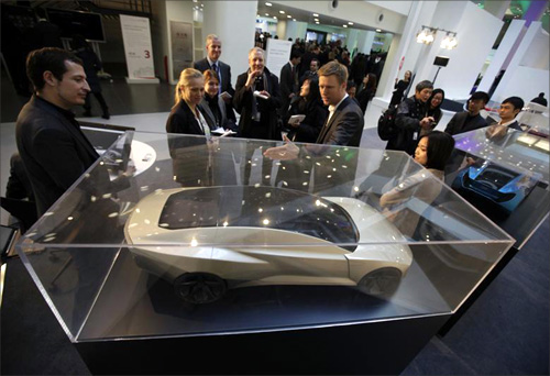 Staff introduce a model of the latest Audi vehicle during a media tour at the opening ceremony of a new Audi China building in Beijing.