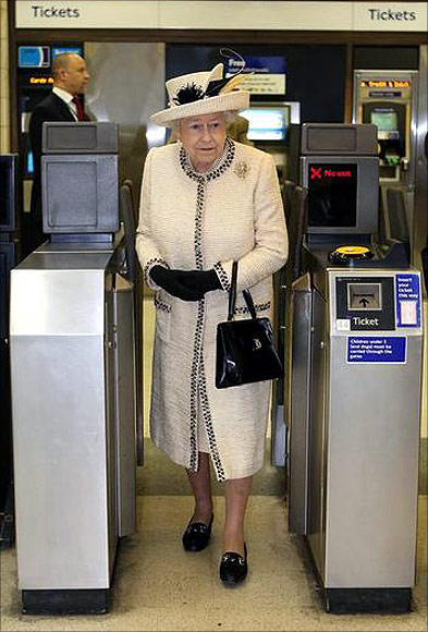 Britain's Queen Elizabeth walks through a ticket barrier during her visit to Baker Street underground station in London.