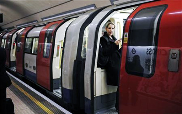 A woman waits for a tube train to depart at an underground station in London.