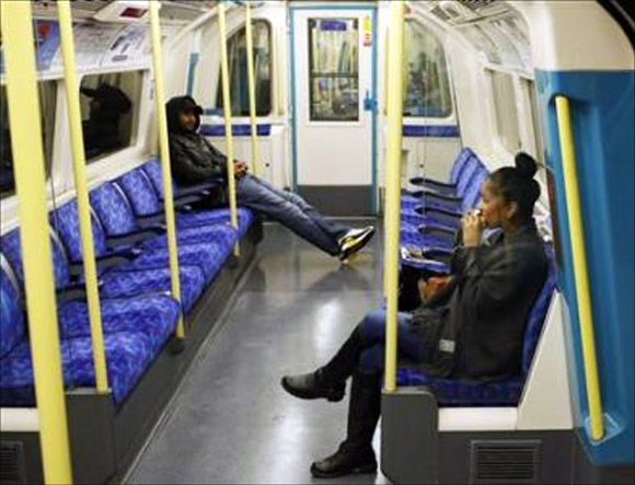 Passengers sit in an underground commuter train in London.